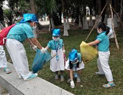 mọi người đang cùng nhau thu gom rác vào xe gom rác